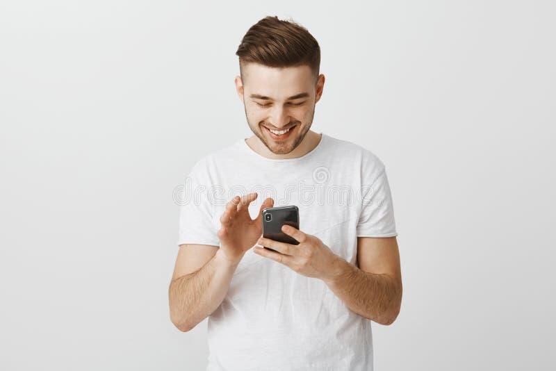 De kerel verzendt grappige meme via smartphone Opgetogen onbezorgd knap mannelijk model met koel kapsel in wit toevallig t stock foto's