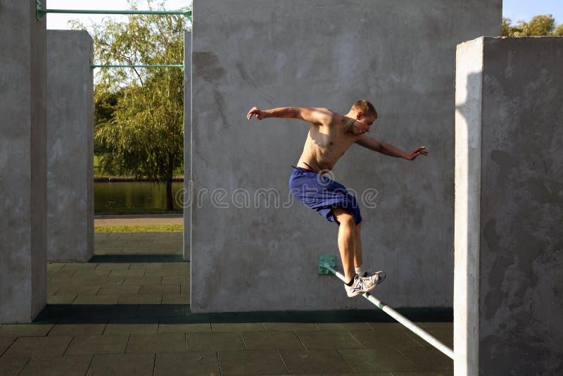 De kerel voert een sprong op de plaats voor het praktizeren uit parkour stock foto's