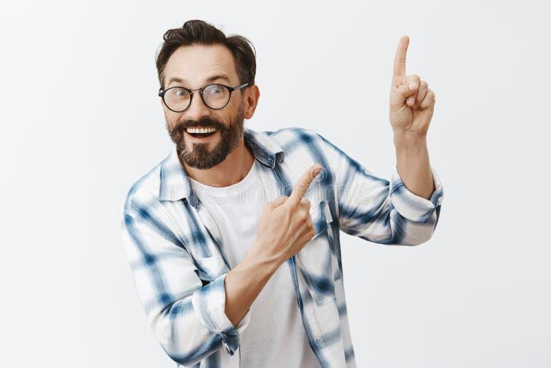 De kerel vond grote machine uit, die het tonen aan professoren Opgewonden en opgewekt het grijnzen mannelijk model met baard en p stock foto's