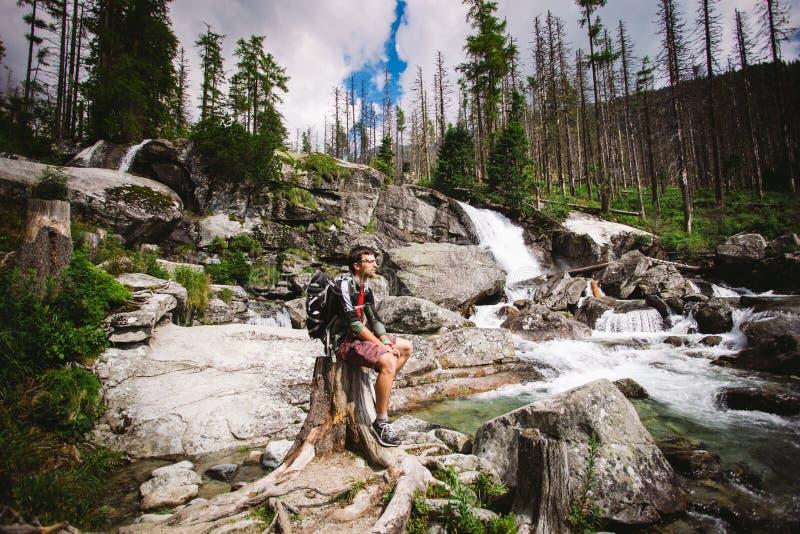 De kerel was een toerist met het zitten op een rots dichtbij de waterval in Slowakije stock foto's