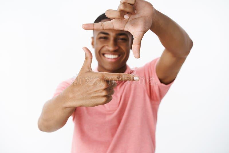 De kerel wil onthoudt meisjeglimlach die handen opheffen die kader met vingers maken en door het glimlachen die van het dromen ge royalty-vrije stock foto