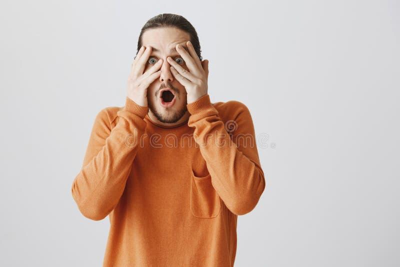 De kerel wil zijn ogen van schok terugtrekken Portret van knappe verraste vriend in oranje sweater die visie behandelen royalty-vrije stock foto's