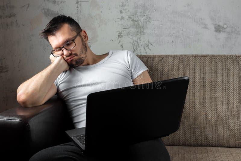 De kerel in de witte overhemdszitting op de laag, viel in slaap bij het werk aangaande laptop Het concept luiheid, apathie royalty-vrije stock fotografie