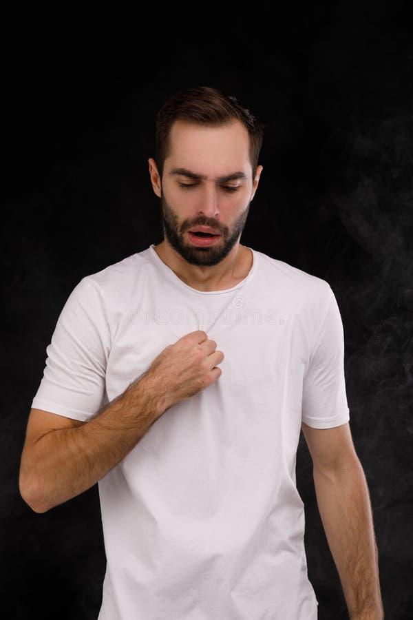 De kerel in de witte T-shirt op de achtergrond van rook stock afbeeldingen