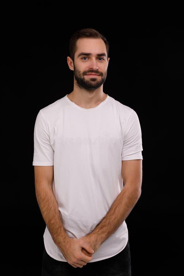 De kerel in de witte T-shirt op een zwarte achtergrond stock foto's