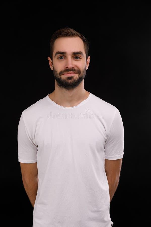 De kerel in de witte T-shirt op een zwarte achtergrond royalty-vrije stock afbeeldingen