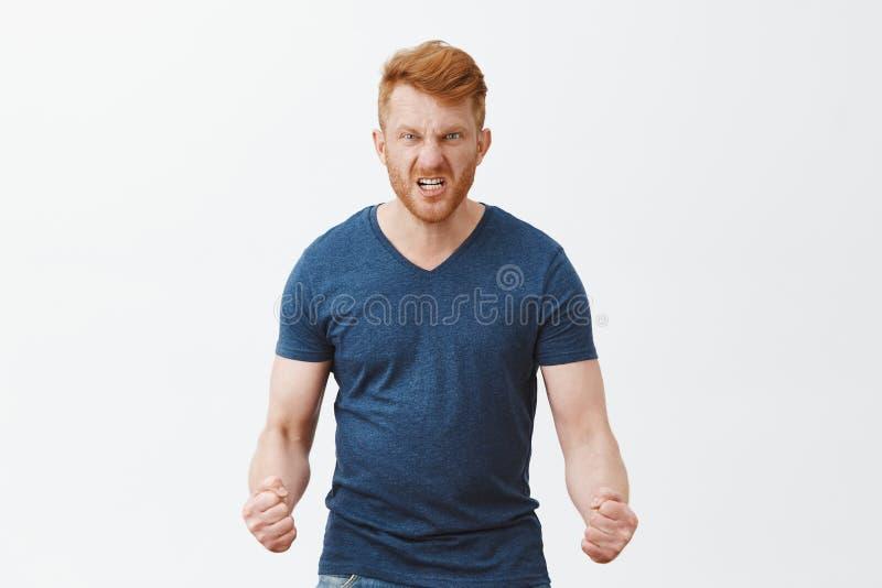 De kerel zal tonen hoe de woede eruit ziet Portret van en boze gevaarlijke roodharigekerel met verbolgen uitdrukking, het rimpele stock foto's