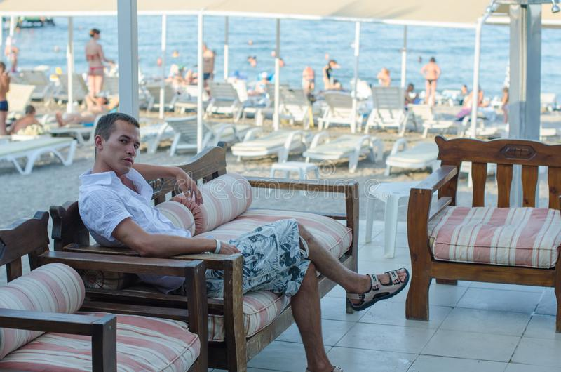 De kerel zit dichtbij het strand in kleren De jonge vermoeide mens rust zitting op een bank door het overzees na een training stock foto's