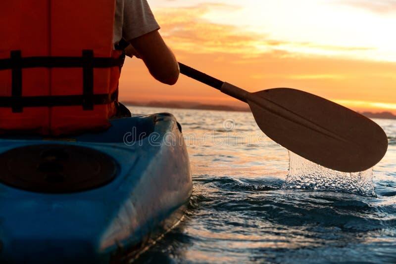 De kerel zit in een kajak in het overzees bij zonsondergang royalty-vrije stock foto's