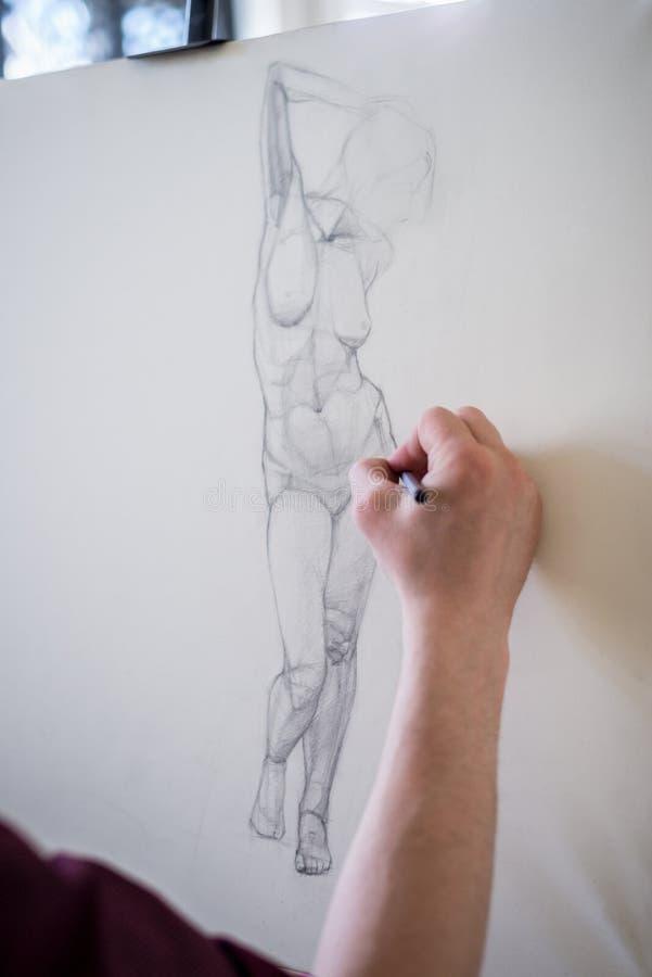 De kerelkunstenaar trekt een mens op een wit groot canvas Verticaal kader royalty-vrije stock afbeeldingen