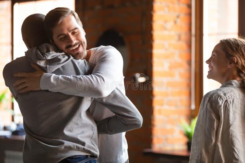 De kerels komen in koffie blij om elkaar te zien samen het omhelzen stock foto's