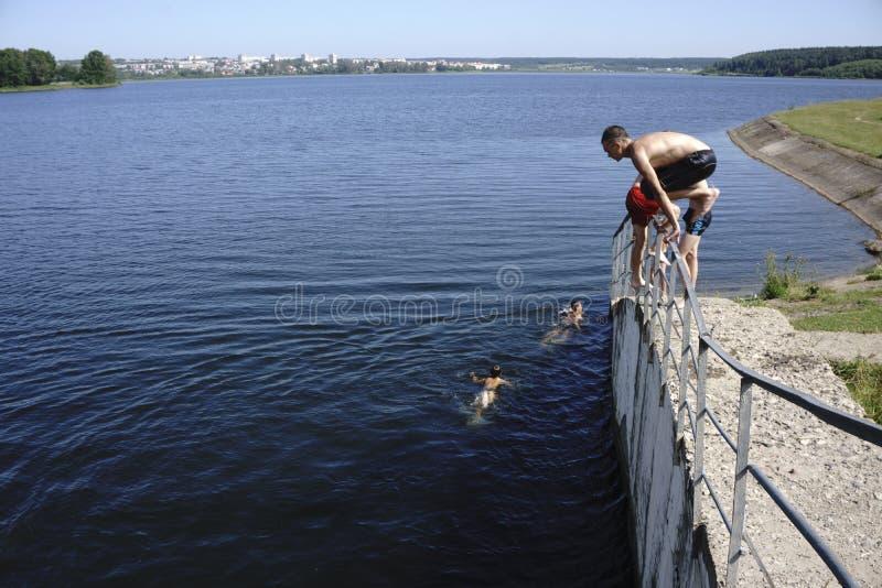 De kerels springen in het water die een bad - Rusland nemen - Berezniki op 31 Juli 2017 stock foto