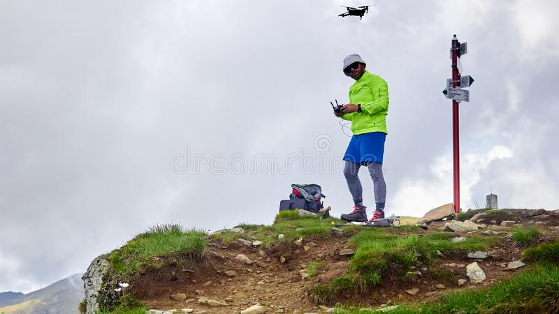 De kereltoerist lanceert quadrocopter in de bergen stock fotografie
