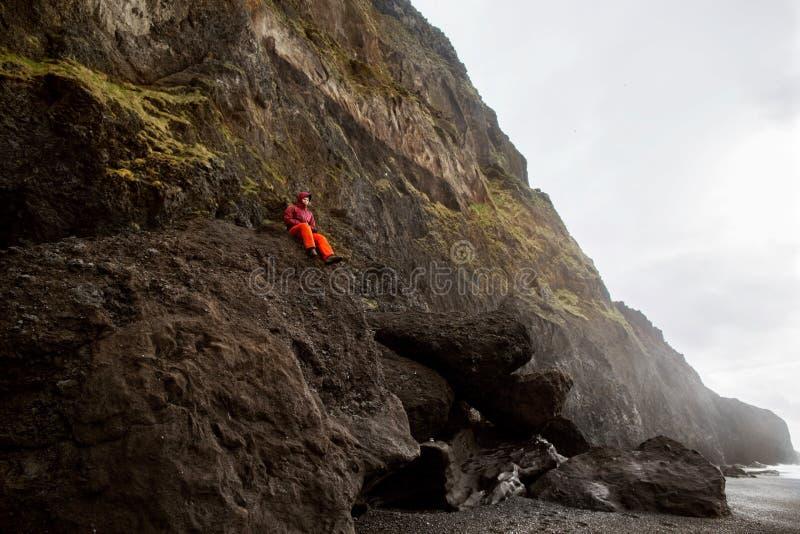 De kereltoerist zit bovenop een berg in IJsland, het concept van royalty-vrije stock afbeelding