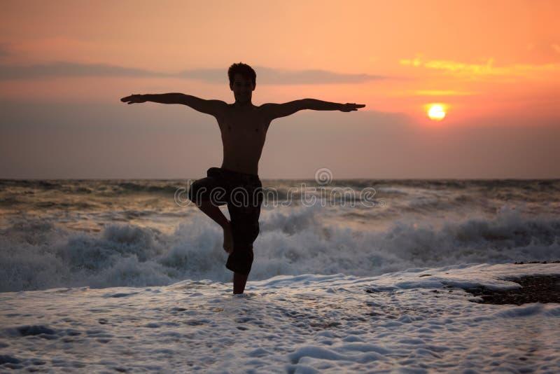 De kerelyoga van het silhouet op zonsondergang golvend strand stock foto's