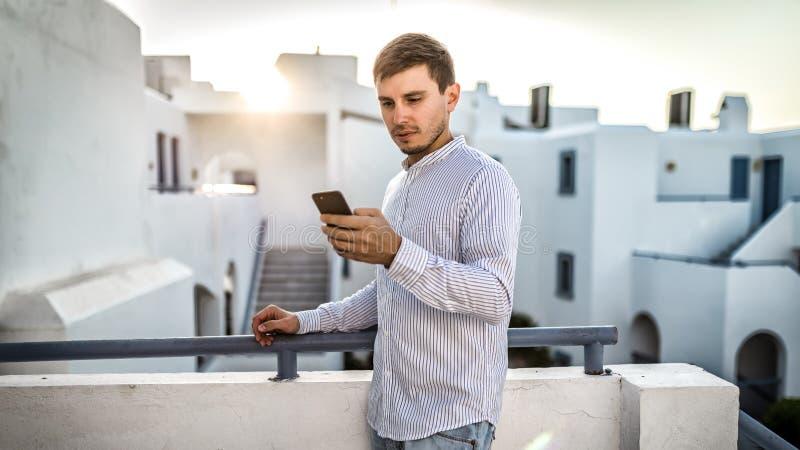 De kerelzakenman de jonge mens de telefoon onderzoekt, draait aantal De witte openluchtzonsondergang Griekenland van de de zomerp royalty-vrije stock afbeeldingen