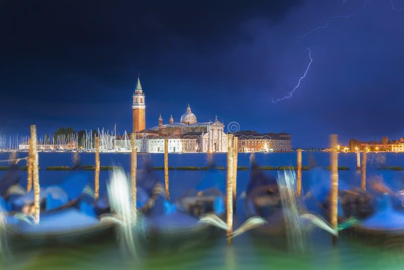 De kerk en de gondels van San Giorgio Maggiore in Venetië, Italië tijdens blauw uur met dramatische hemel en verlichting Nadruk o stock fotografie