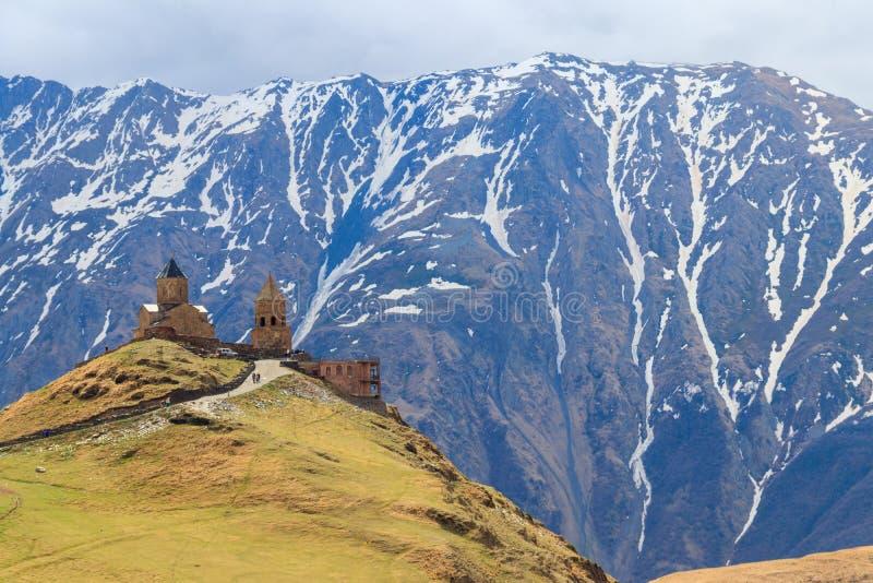 De Kerk Tsminda Sameba, Heilige Drievuldigheidskerk van de Gergetidrievuldigheid dichtbij dorp van Gergeti in Kaukasische bergen, stock foto