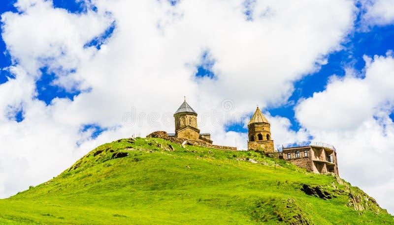 De Kerk van de Gergetidrievuldigheid - Tsminda Sameba - dichtbij het dorp van Gergeti in Georgië, zet onder Kazbegi op royalty-vrije stock afbeelding