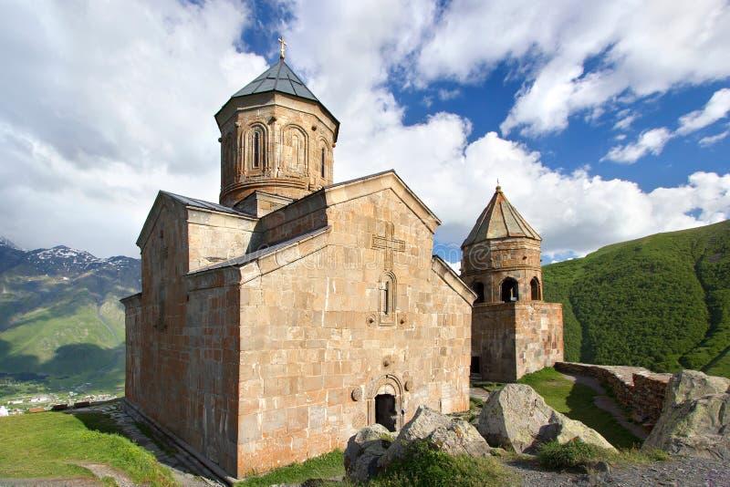 De Kerk van de Gergetidrievuldigheid, Tsminda Sameba op blauwe hemel met wolkenachtergrond in Georgië royalty-vrije stock afbeeldingen