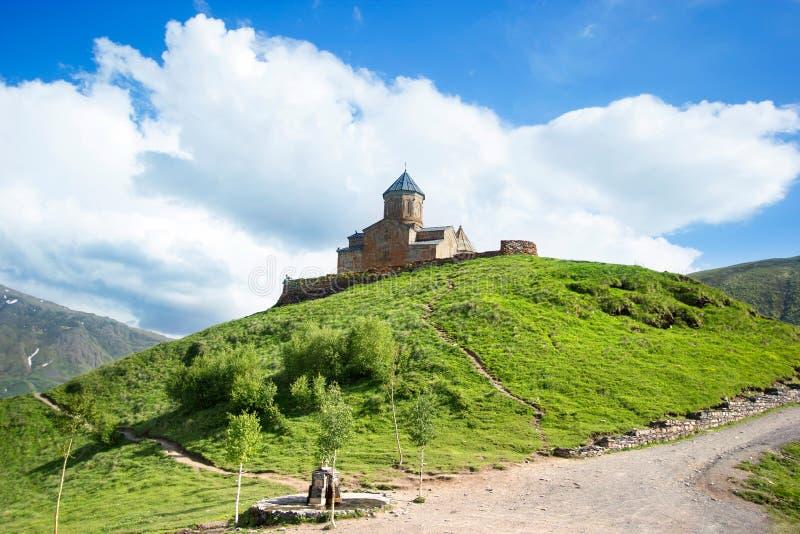 De Kerk van de Gergetidrievuldigheid, Tsminda Sameba op de heuvel dichtbij Kazbek-berg in Georgië stock foto's