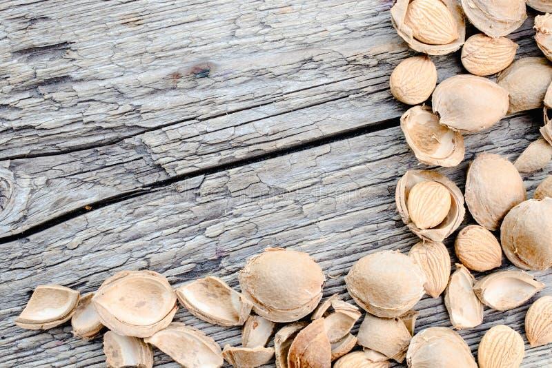 De kern van abrikozen en stenen op de achtergrond van oude raad Abrikozenkuilen voor de vervaardiging van tabletten en drugs stock foto's
