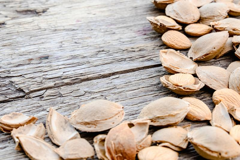 De kern van abrikozen en stenen op de achtergrond van oude raad Abrikozenkuilen voor de vervaardiging van tabletten en drugs royalty-vrije stock foto