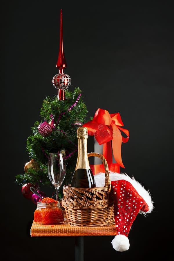 De Kerstboom, fles wijn, bank met rode kaviaar en de attributen van het Nieuwjaar stock foto's