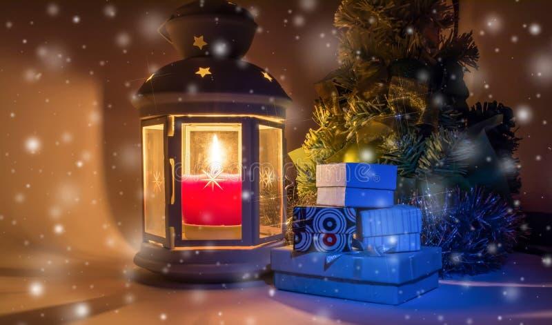 De kerstboom met giftdozen en de oude uitstekende lantaarn met het branden van kaars en met mooi glanzen als ster op een dalende  royalty-vrije stock afbeeldingen