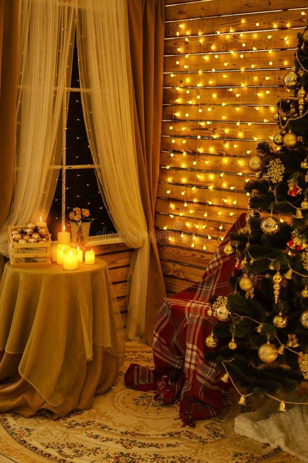 De kerstboom is in de ruimte op de muur hangende slingers, een lijst door het venster met kaarsen stock fotografie