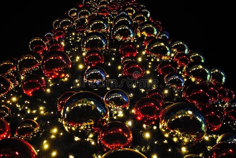 De kerstboom verfraaide met lichten en kleurde gebieden stock afbeelding