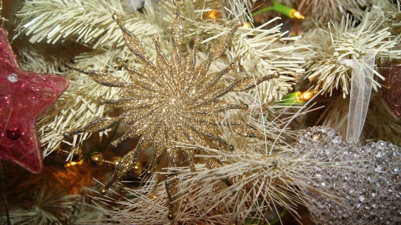 De kerstboomdecoratie in spiraalvormige die stervorm van glanzende gouden wordt gemaakt schittert het hangen van de boom Macro fo royalty-vrije stock fotografie
