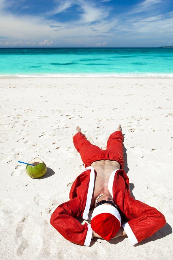 De Kerstman bij strand het ontspannen stock afbeelding