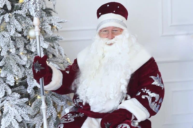 De Kerstman dichtbij Kerstmisboom bij Kerstmis stock foto's