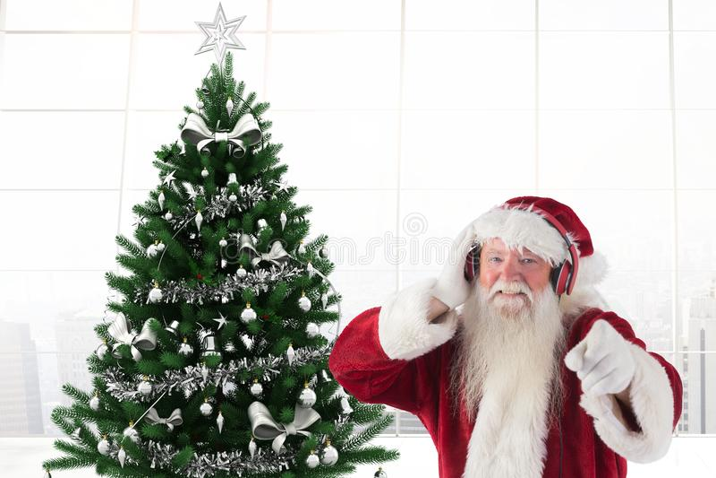 De Kerstman die aan muziek bij hoofdtelefoons en het gesturing luisteren stock fotografie