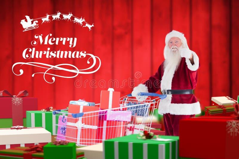 De Kerstman die duimen tonen terwijl het houden van boodschappenwagentjehoogtepunt van giften royalty-vrije stock afbeeldingen