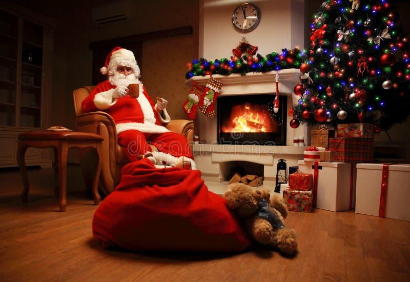 De Kerstman die een rust als comfortabele voorzitter heeft dichtbij de open haard thuis royalty-vrije stock afbeelding