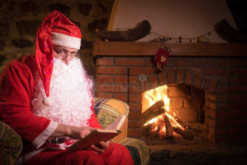 De Kerstman die een rust als comfortabele voorzitter heeft dichtbij de open haard thuis stock foto's