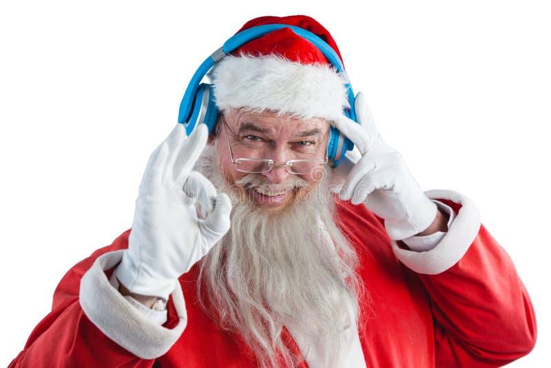 De Kerstman die hand o.k. teken tonen terwijl het luisteren aan muziek op hoofdtelefoons stock foto's