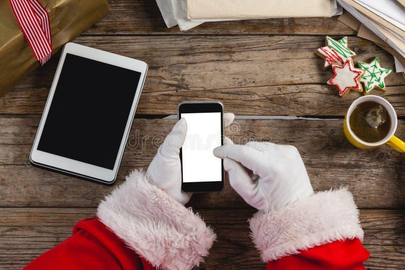 De Kerstman die mobiele telefoon met behulp van stock foto