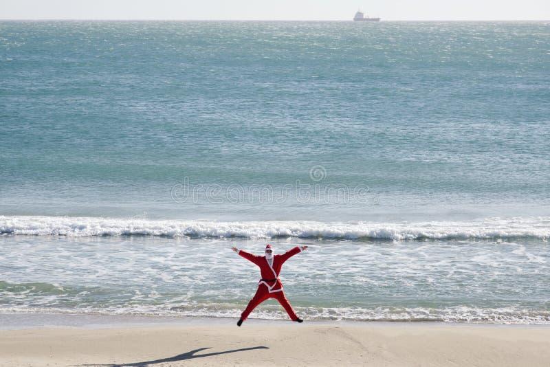 De Kerstman die op het strand springen stock foto's