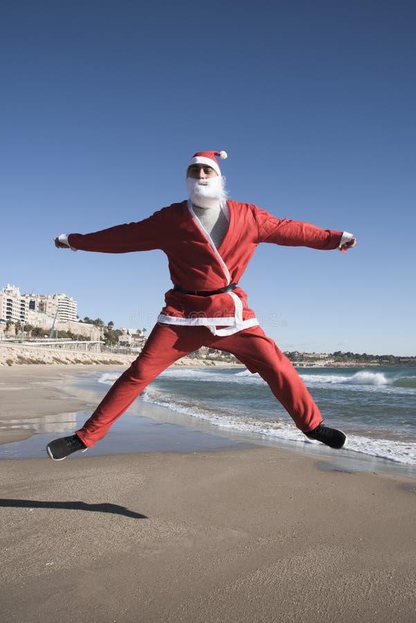 De Kerstman die op het strand springen royalty-vrije stock afbeeldingen