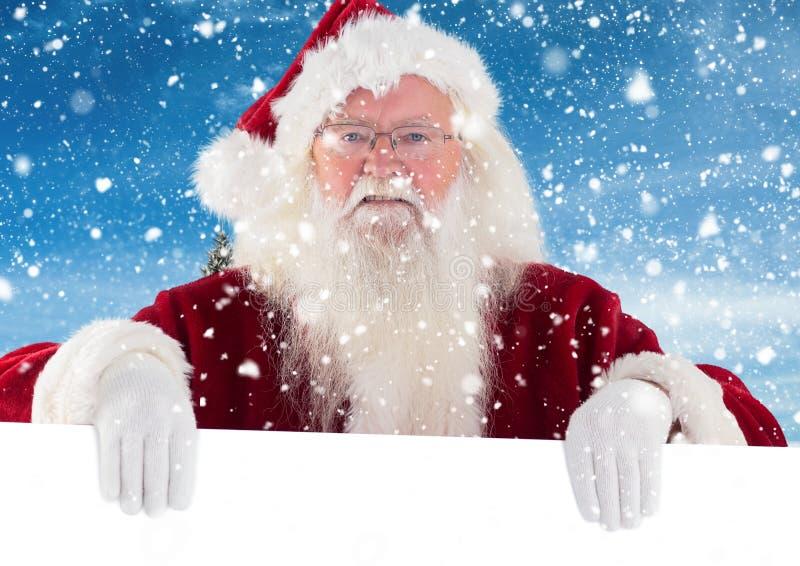 De Kerstman die wit aanplakbiljet houden stock foto's