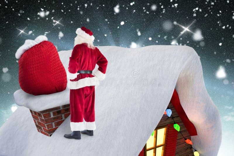 De Kerstman die zich op de dakbovenkant bevinden met zijn giftzak stock foto