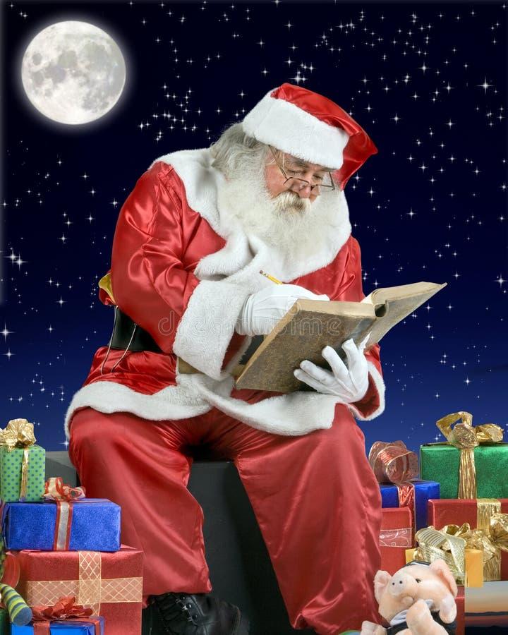 De Kerstman die zijn notitieboekje op het dak van a schrijft stock fotografie
