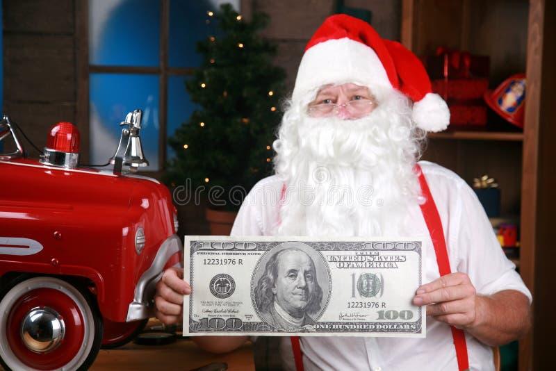 De kerstman houdt een reuze honderd dollarrekening stock foto
