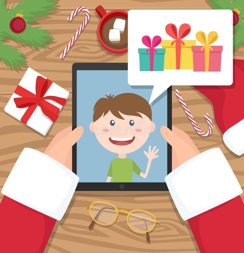 De Kerstman houdt tablet en heeft gesprek met jong jong geitje dat over giften spreekt die hij zou willen om bij Kerstmis krijgen royalty-vrije stock afbeeldingen