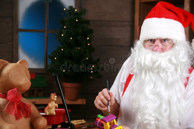 De kerstman maakt speelgoed in zijn workshop royalty-vrije stock afbeelding
