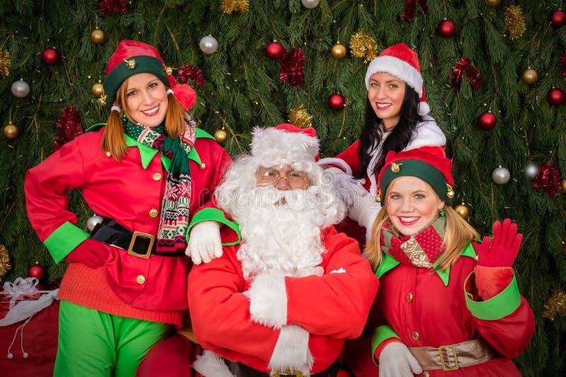 De Kerstman met de vrouwenkerstmis van de elfhelper stock afbeelding