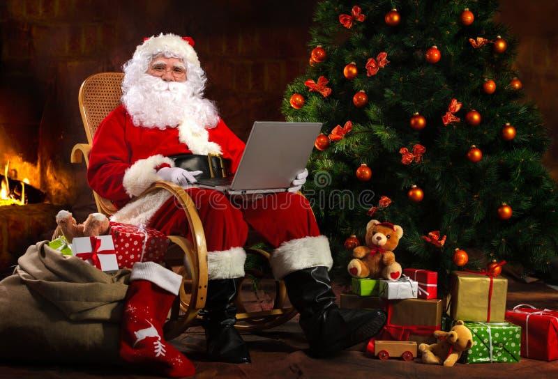 De Kerstman met laptop stock fotografie